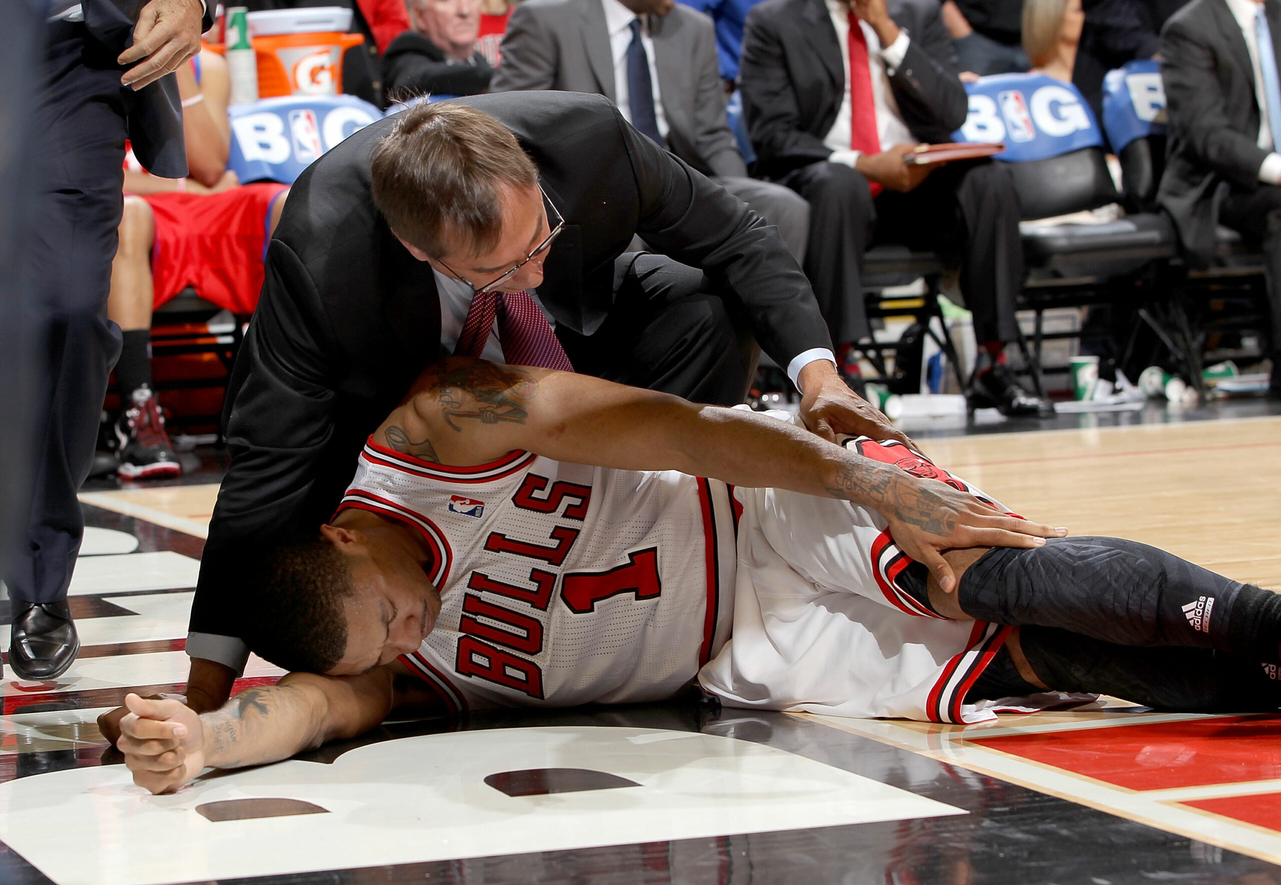 Chicago Bulls Head Athletic Trainer Fred Tedeschi assists Derrick Rose #1 after injuring his knee against the Philadelphia 76ers in Game One of the Eastern Conference Quarterfinals during the 2012 NBA Playoffs on April 28