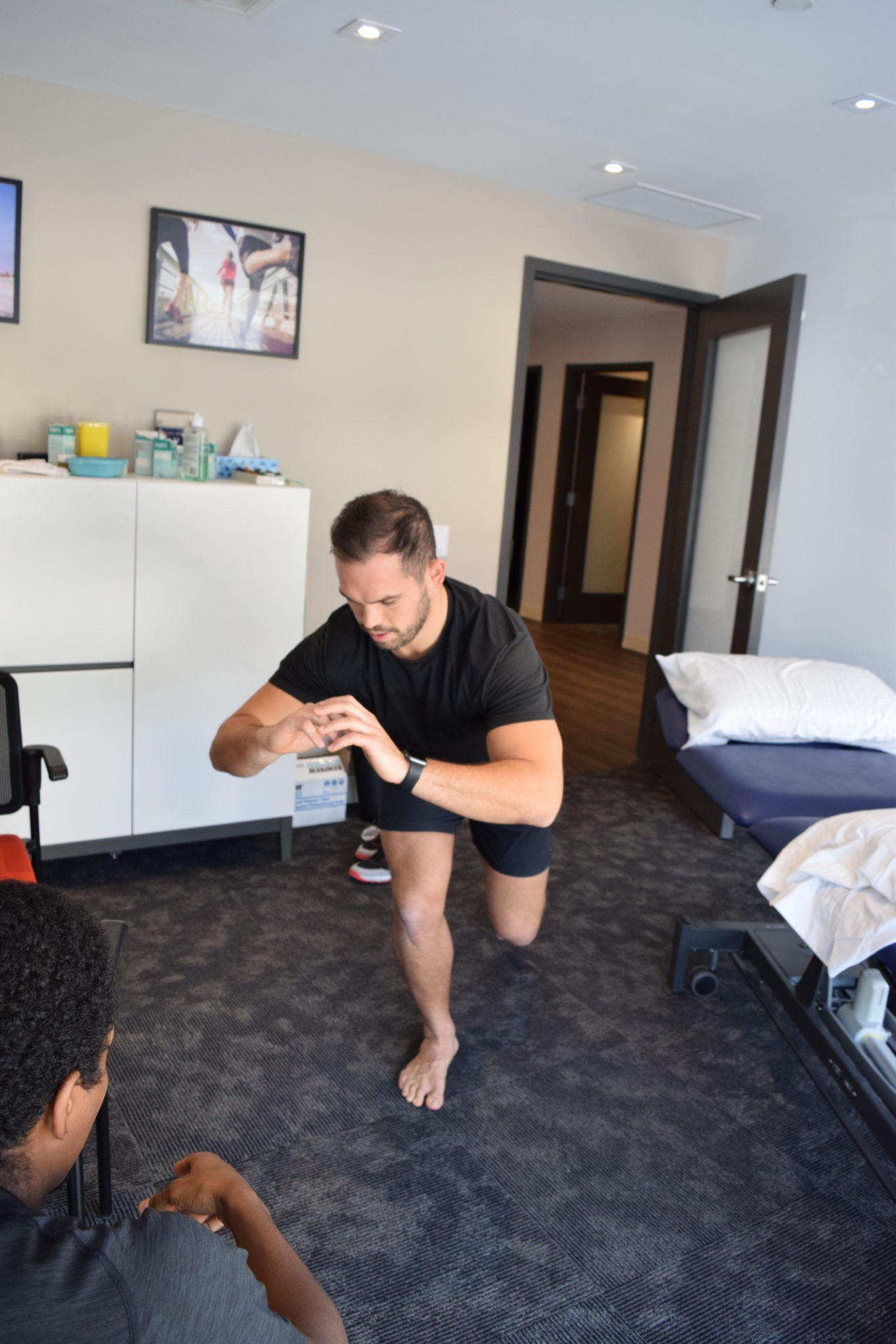 Man performing a single leg squat while a physiotherapist watches|Dan Pringle