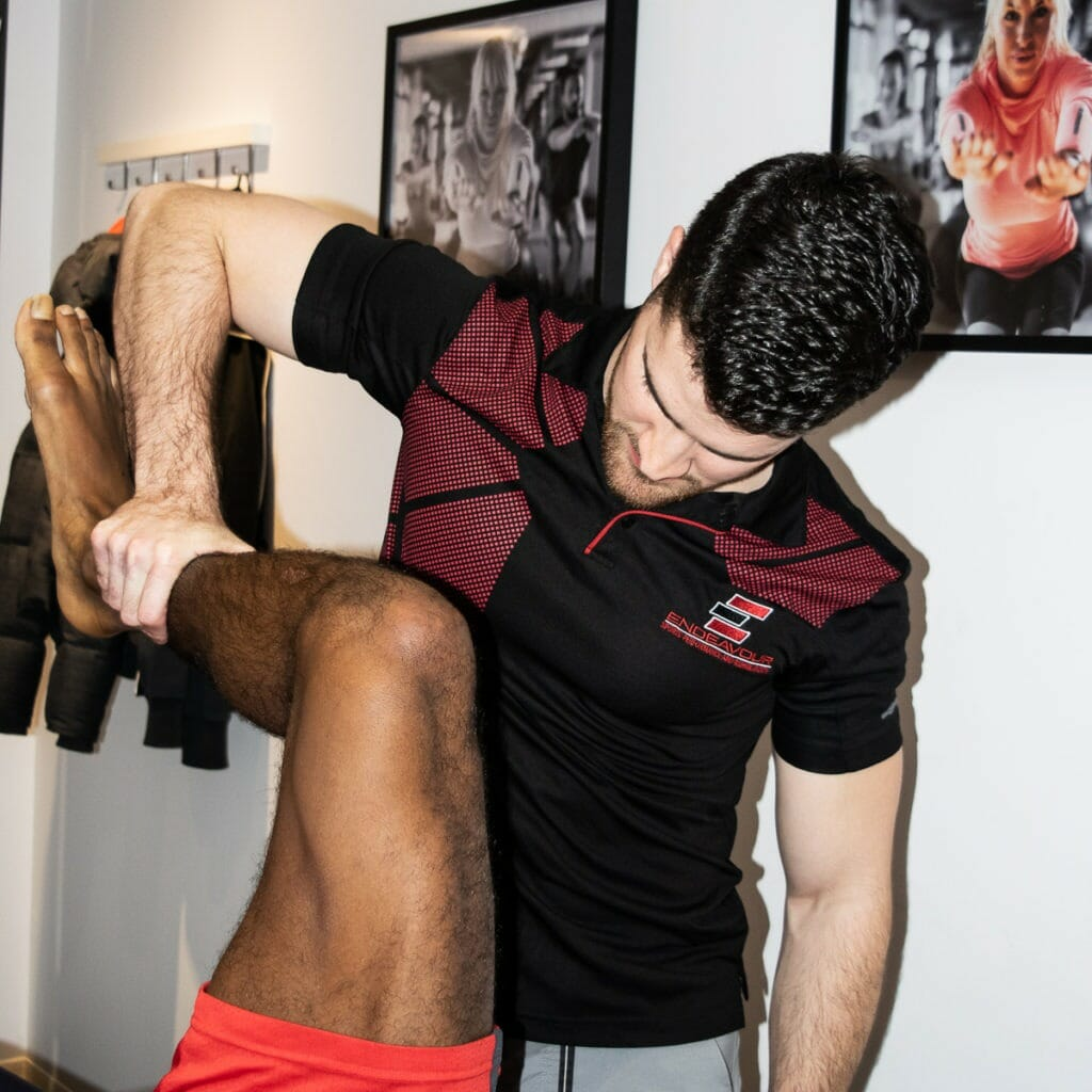 Physiotherapist testing the strength of a man's leg