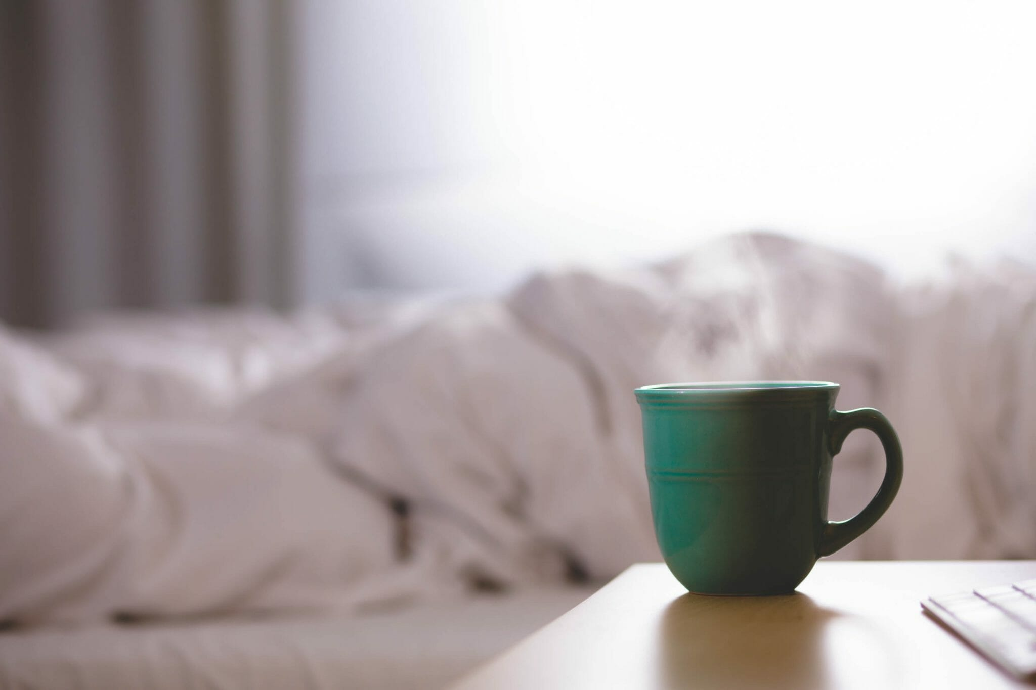 Mug on table next to bed|||